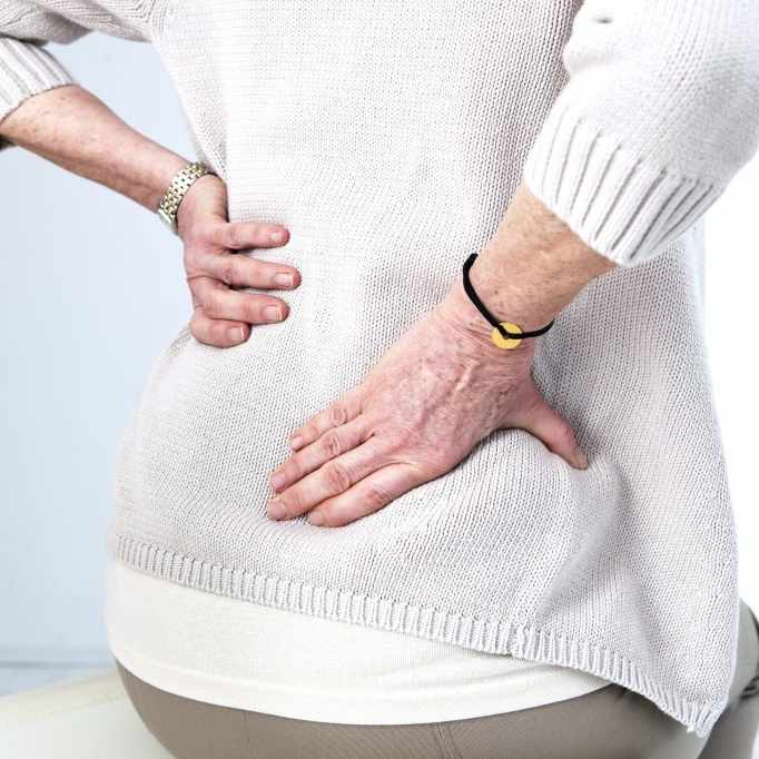 older woman holder her lower back, suffering with low back pain