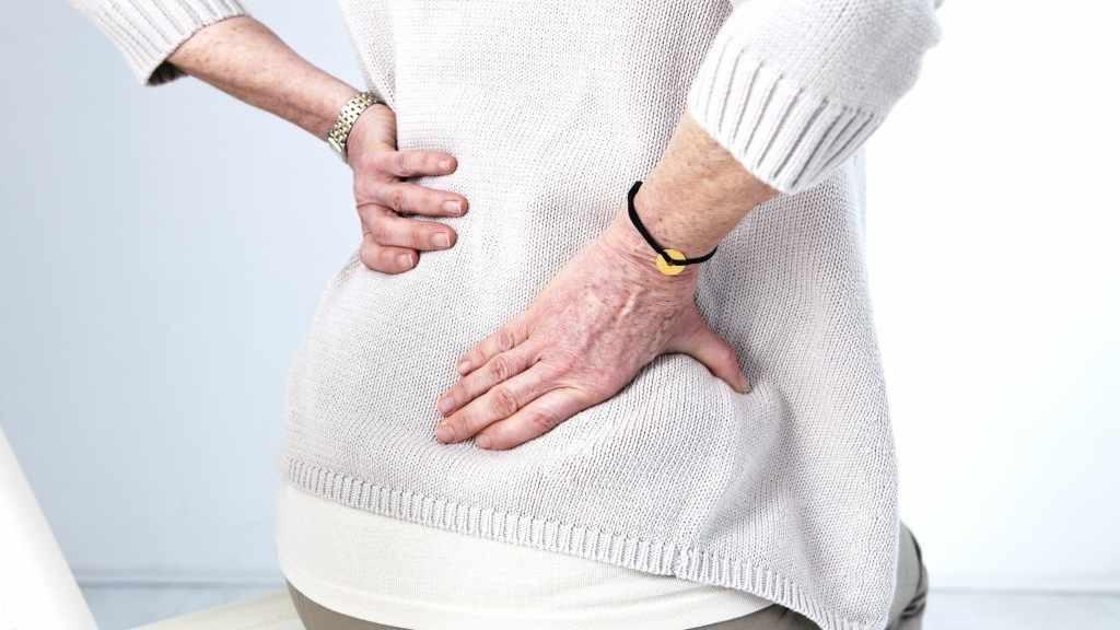 mujer mayor sostiene su espalda baja, sufriendo de dolor lumbar