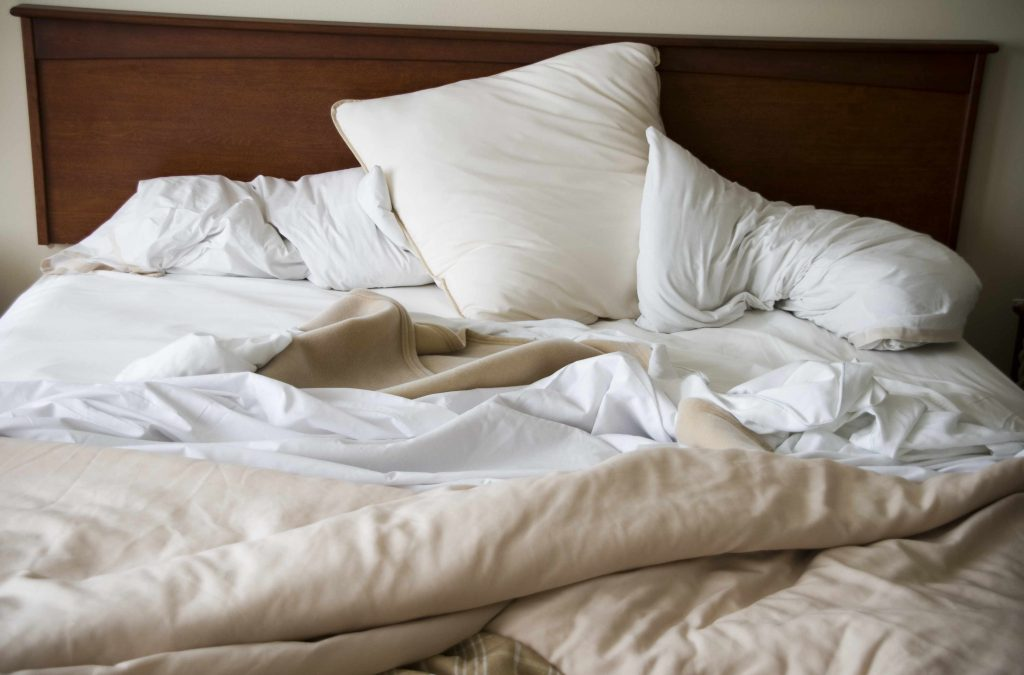 a messy, unmade bed with pillows, blankets and sheets