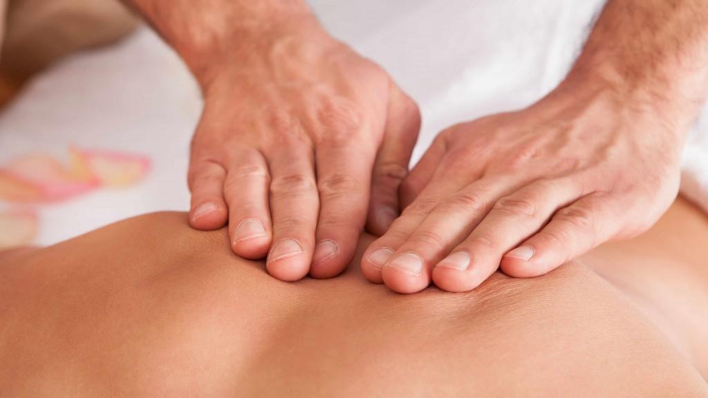 Dos manos presionan sobre una espalda desnuda