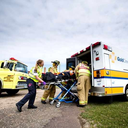 emergency medical technicians loading patient into ambulance
