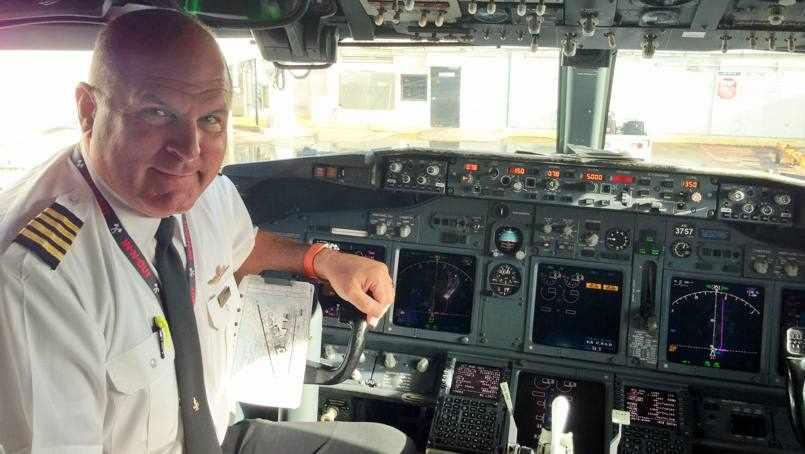chronic pain patient Perry Winder in his pilot uniform sitting a plane cockpit