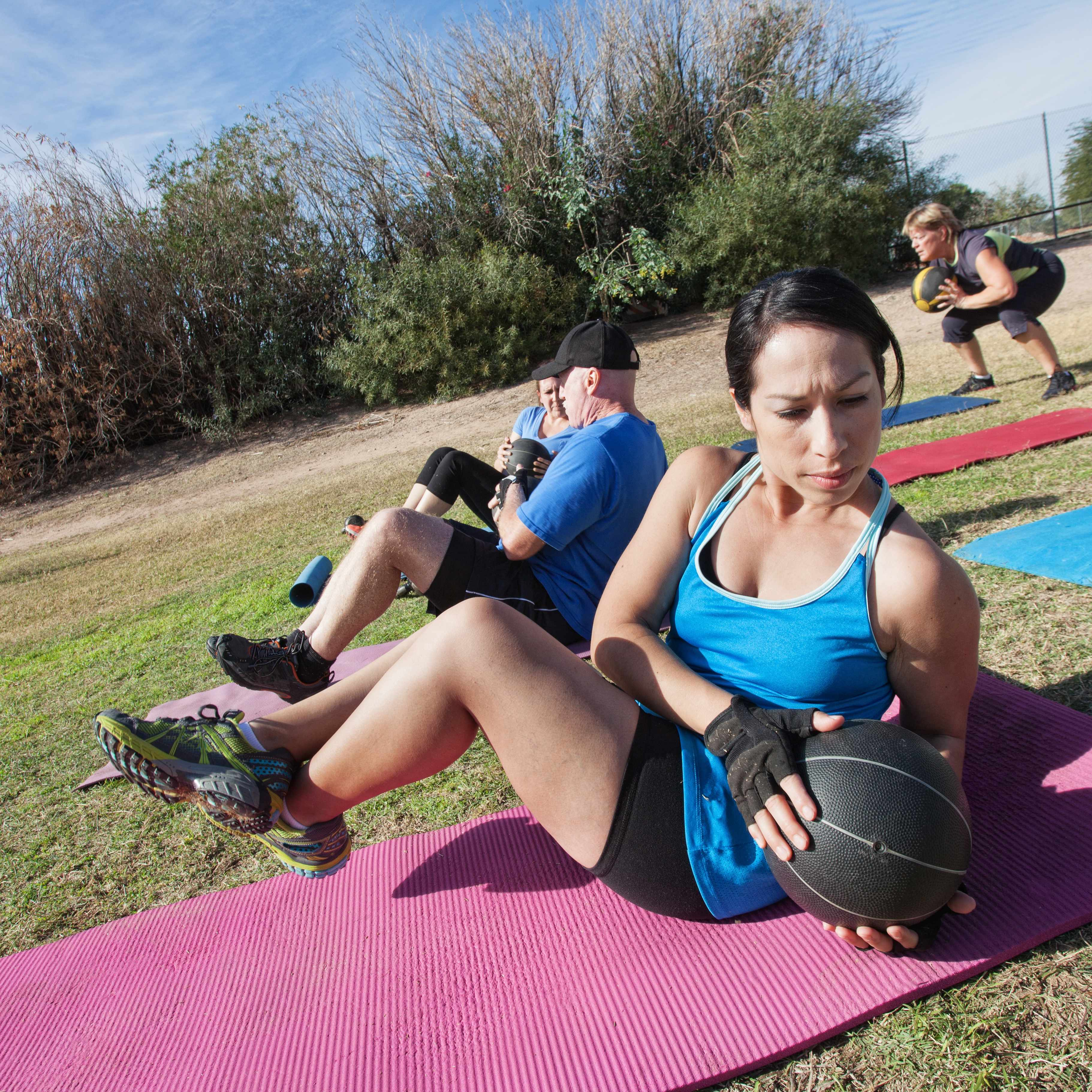 a group of people outside working out, strengthing core muscles