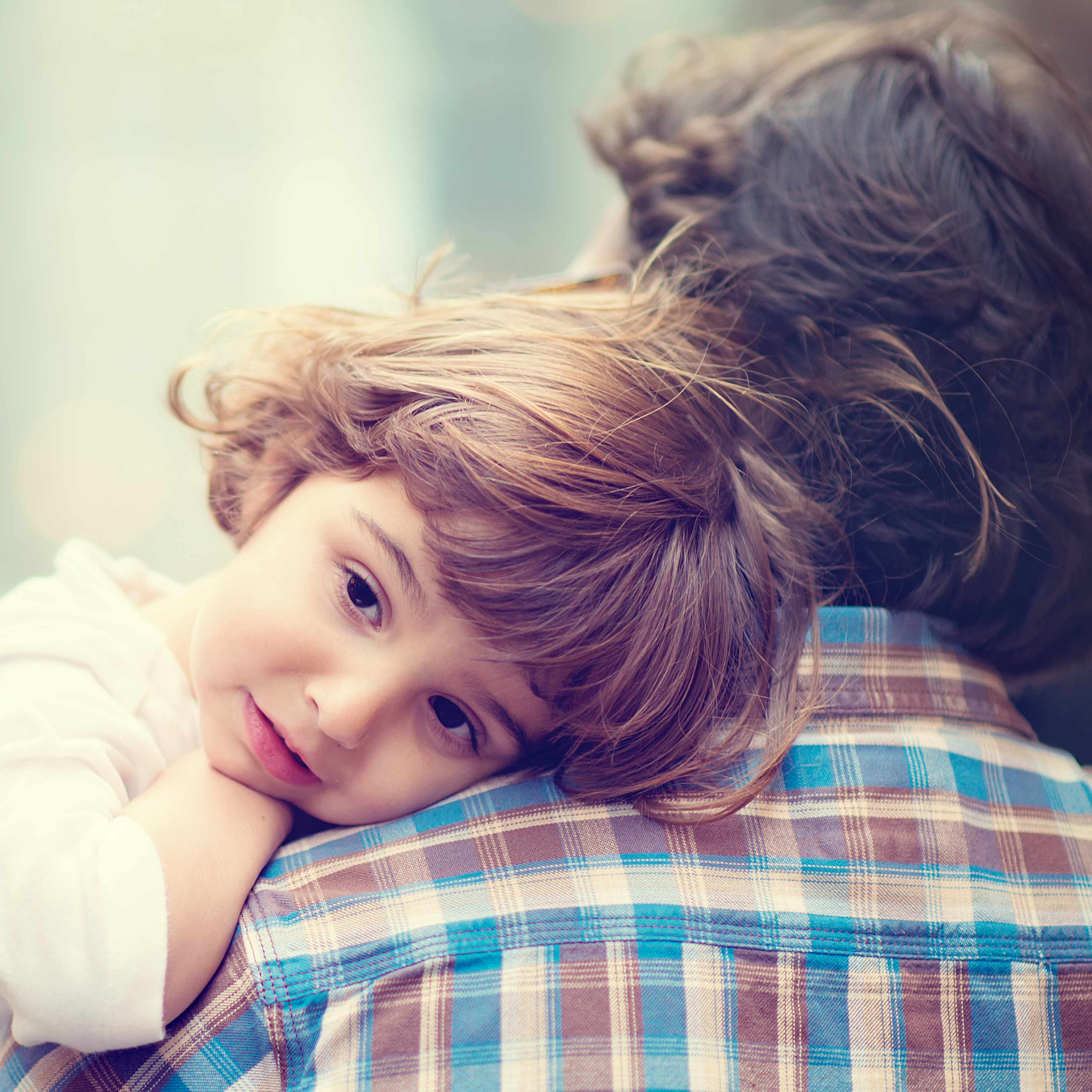 little girl in a adult person's arms resting her head on his shoulde