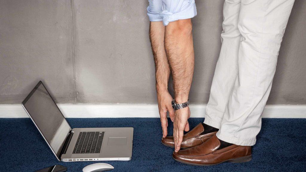 Un hombre hace ejercicios en la oficina y pone el computador portátil en el piso para tocarse los dedos de los pies