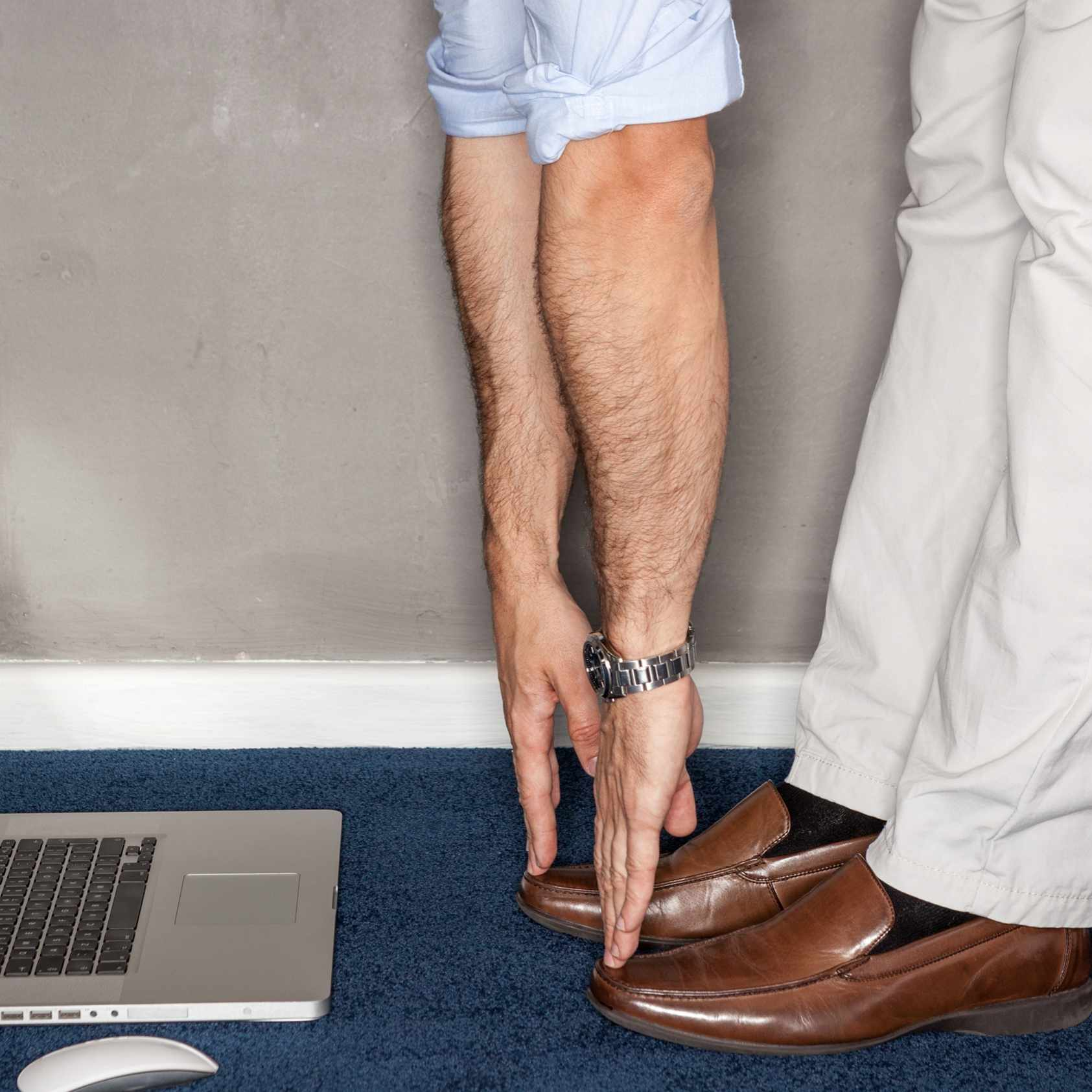 a man standing in his office doing exercises with laptop on floor, touching his toes