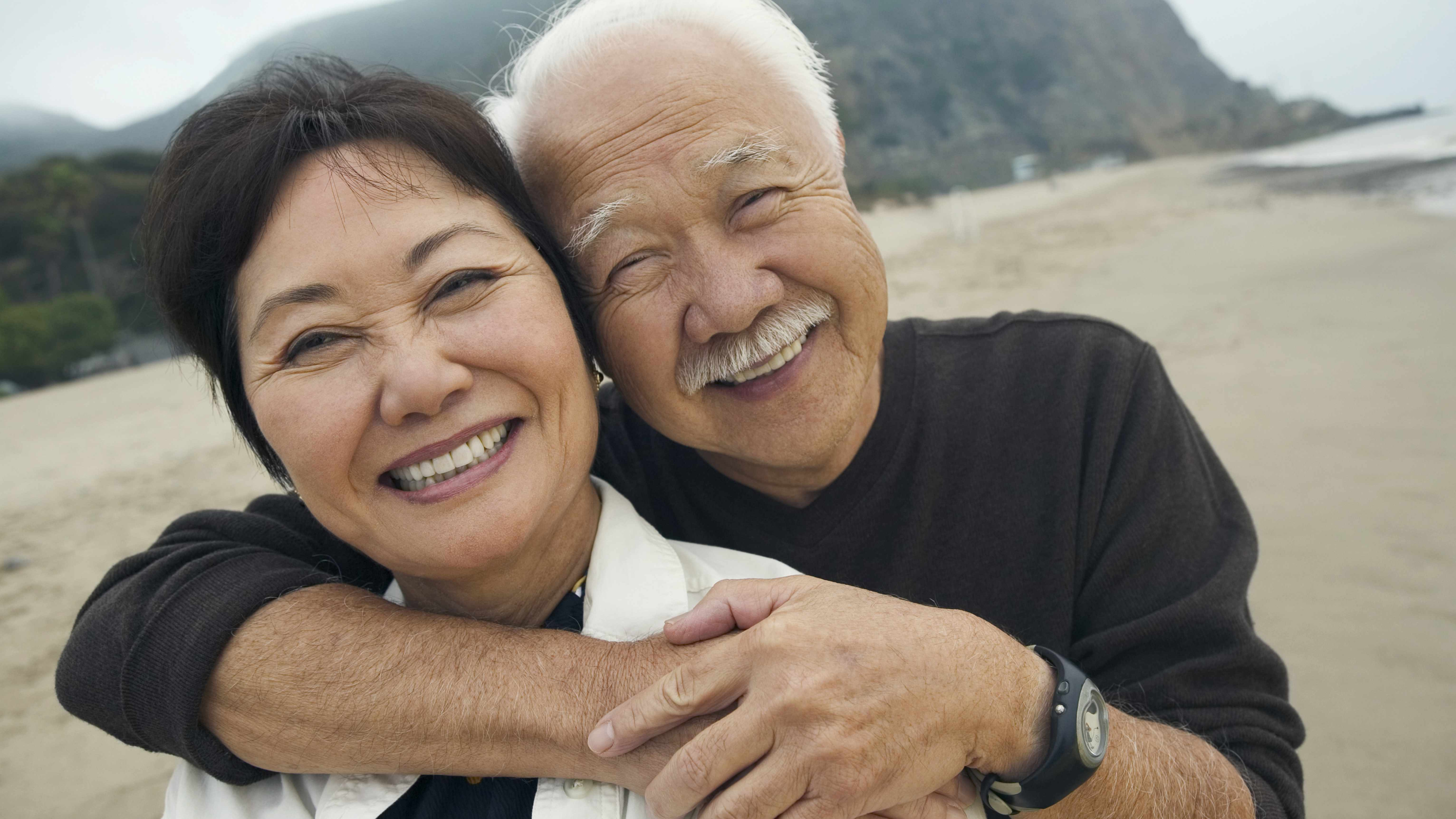 Un hombre y una mujer de mediana edad sonreídos y abrazados en la playa