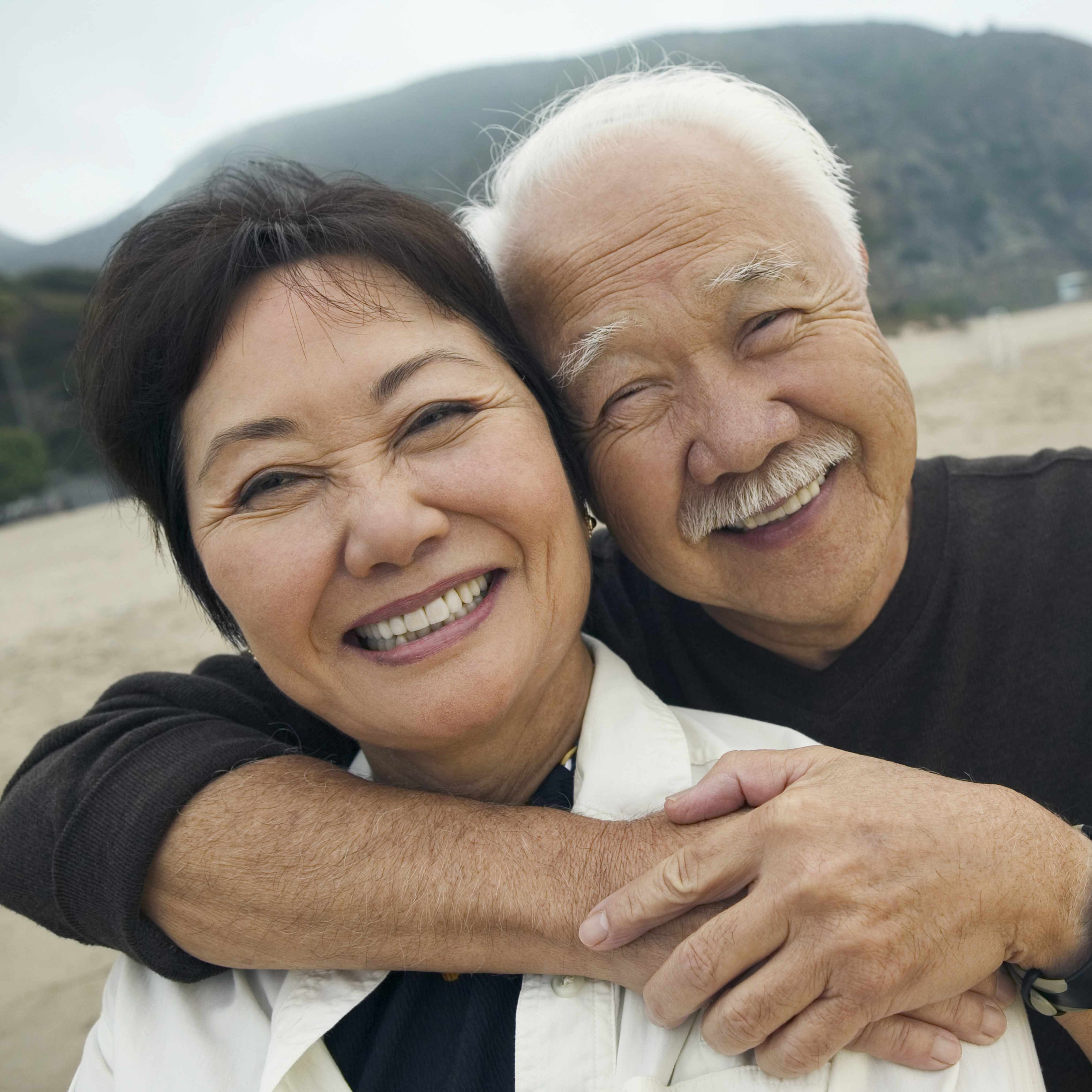a close-up of a smilng senior couple on a beach, with the man's arms around the woman's shoulders