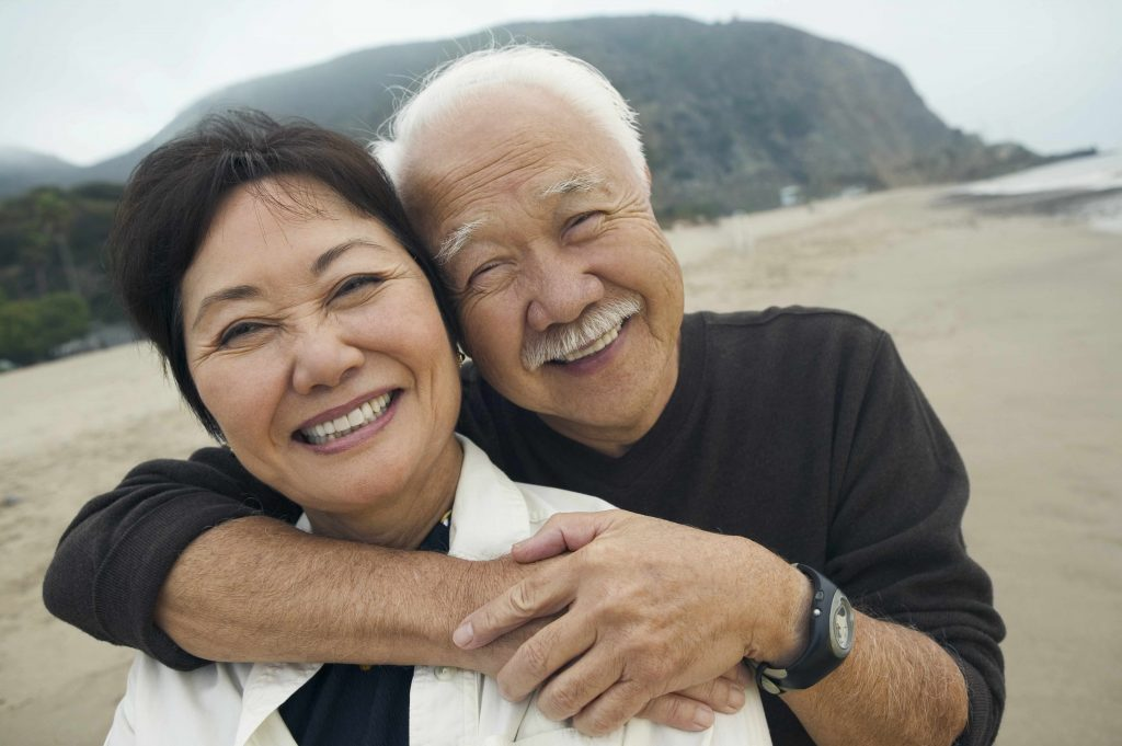 a middle-aged woman and man on the beach, smiling and embracing