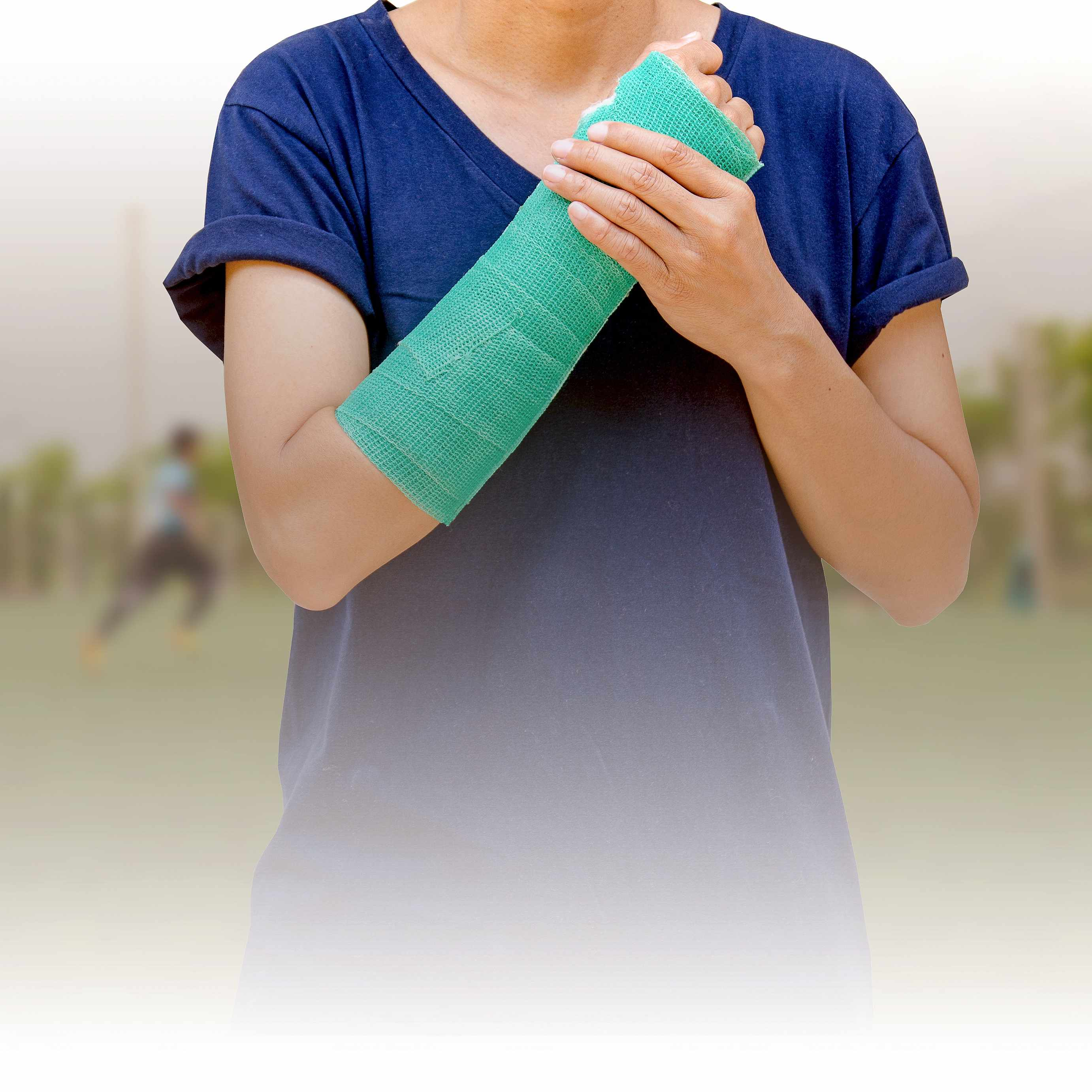 a teenager with a cast on the arm, wrist to elbow, standing in front of other teenagers playing soccer