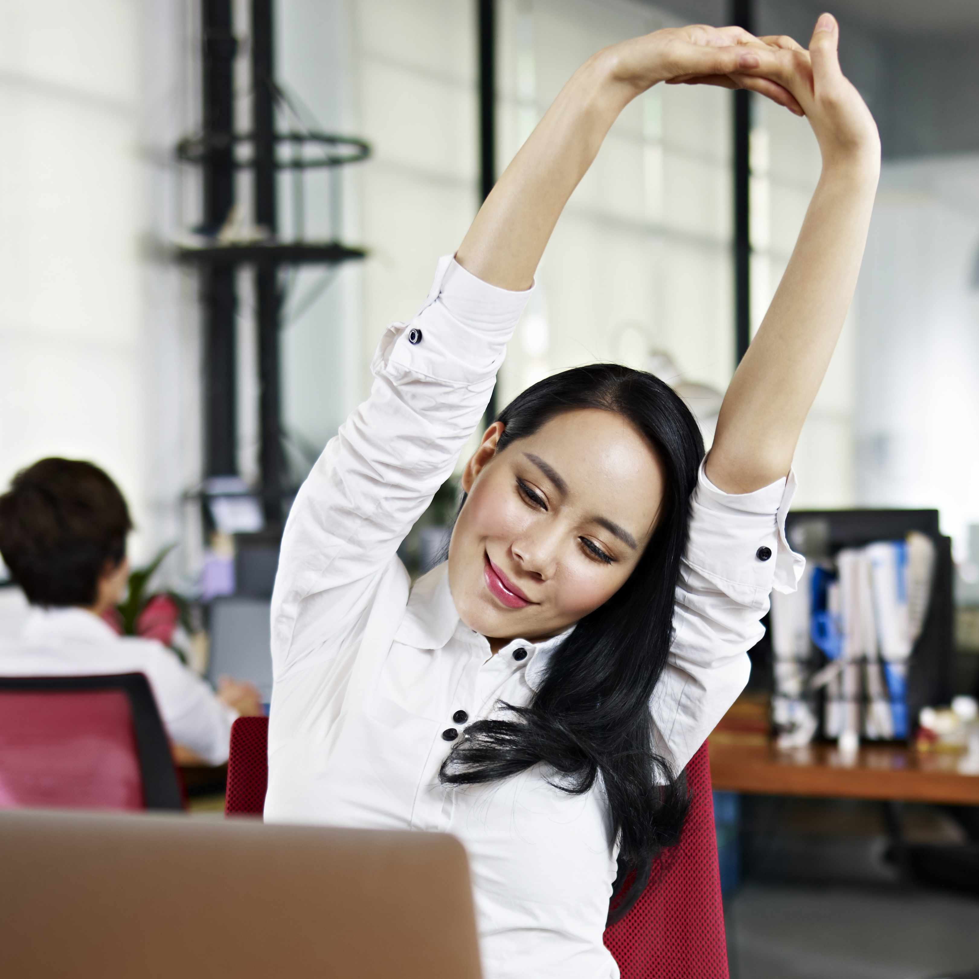 a young woman working in her office, stretching and exercising at her desk