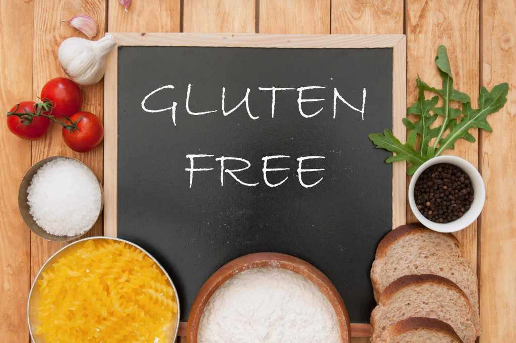 "the words ""gluten free"" written on a chalkboard surrounded by bread, pasta and vegetables"