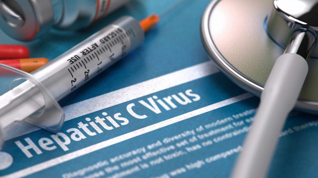 hepatitis C virus written on blue background with pills, syringe and stethoscope