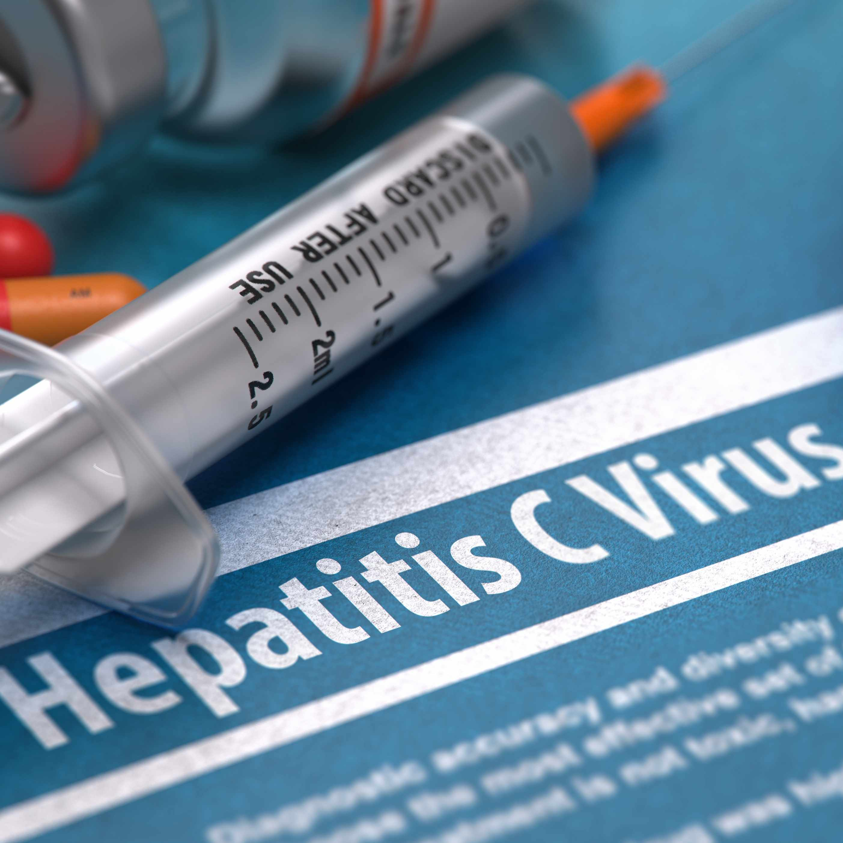 hepatitis C virus written on blue background with pills, syringe and stethoscope