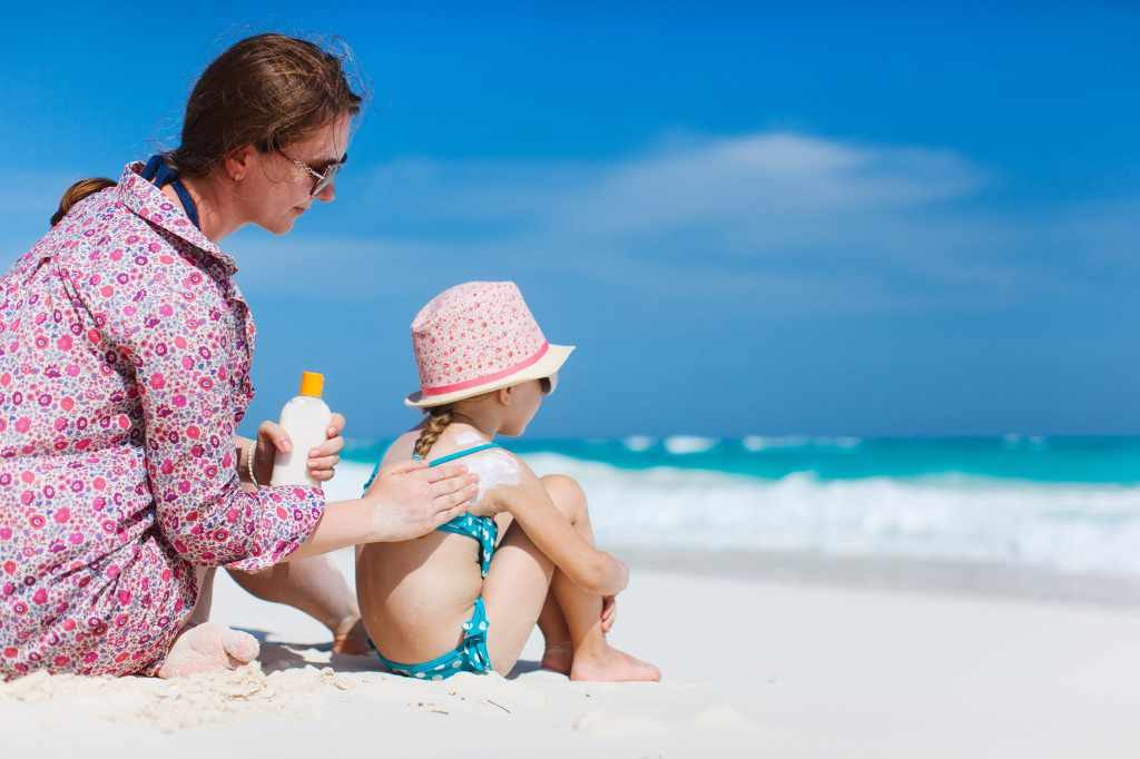 a mother applies sunscreen to a young child on the beach