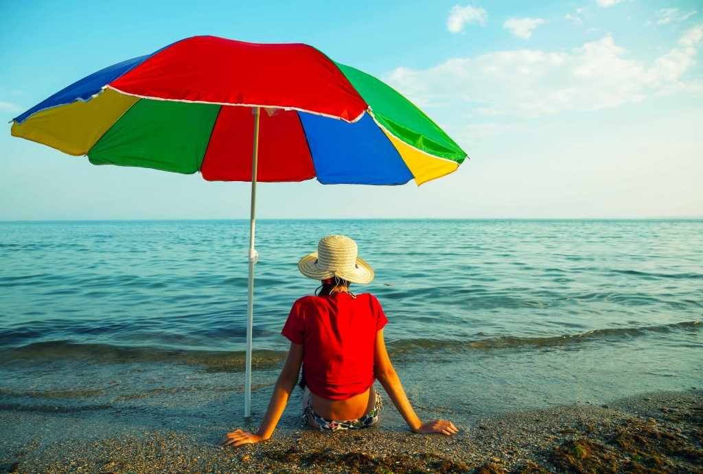 a person sitting on the beach in a hat, under the shade of an umbrella