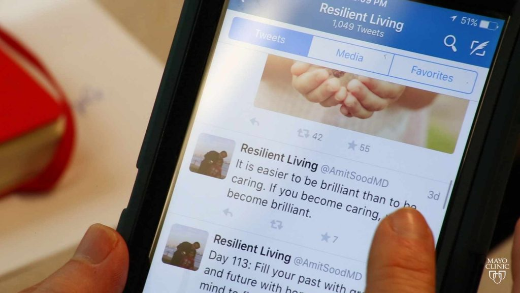 a hand holding a smart phone with the twitter Dr. Sood resilient living tweets on screen