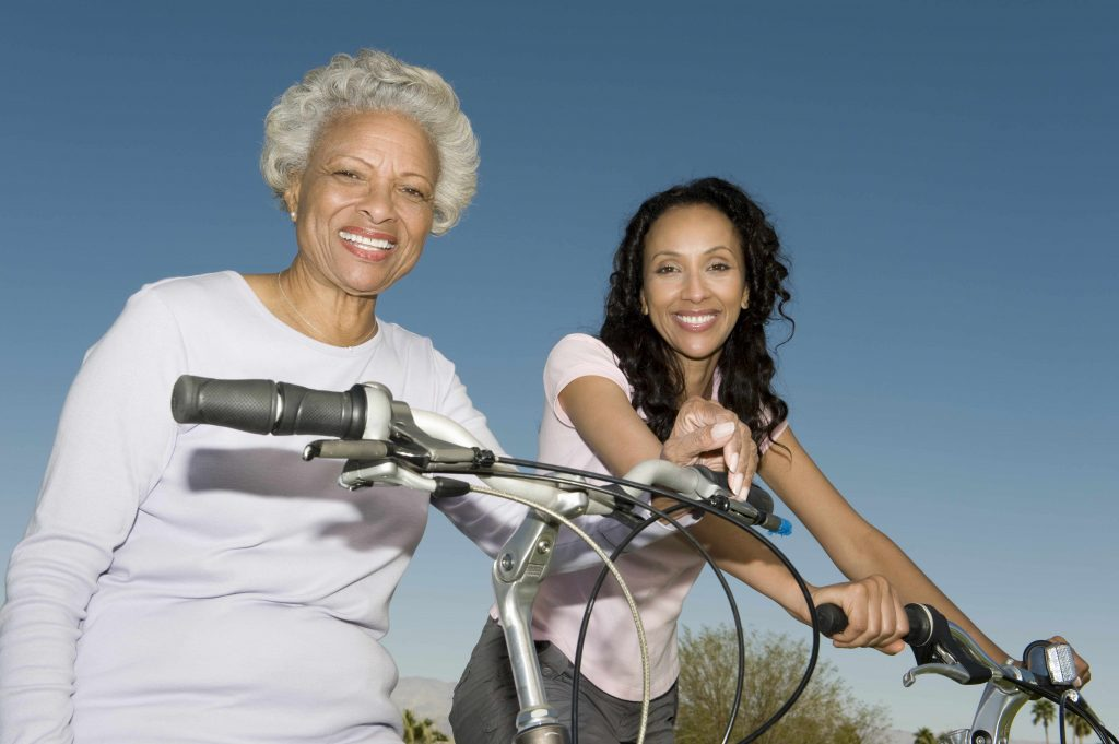 an African American mother and daughter sitting on bicycle against blue sky and smiling