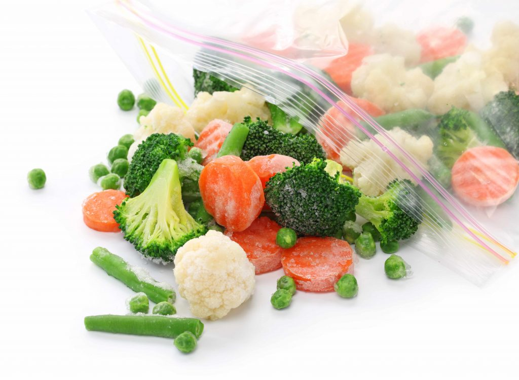 a plastic bag with frozen vegetables spilling out, carrots, peas, broccoli