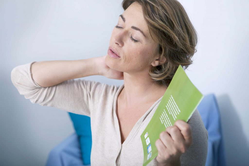 a middle-aged woman rubbing her neck and fanning herself, perhaps sweating with menopausal hot flashes