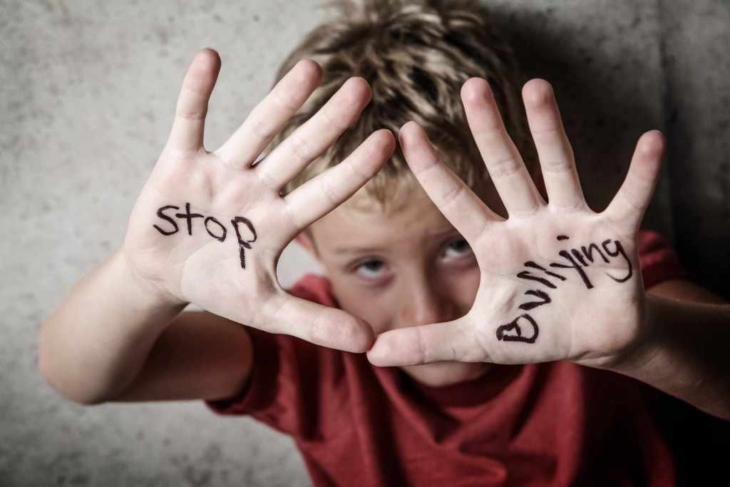 a child with stop bullying written on his hands