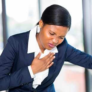 young business woman holding chest appearing to have heart attack