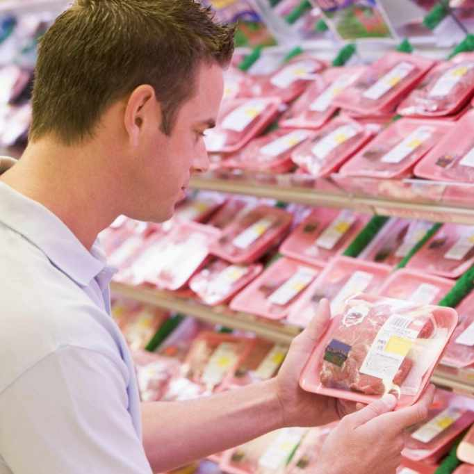 a man looking at packages of meat and reading the labels in a grocery store