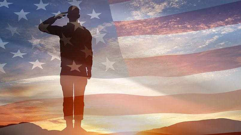 a soldier salutely at sunset with the United States flag superimposed over the photo