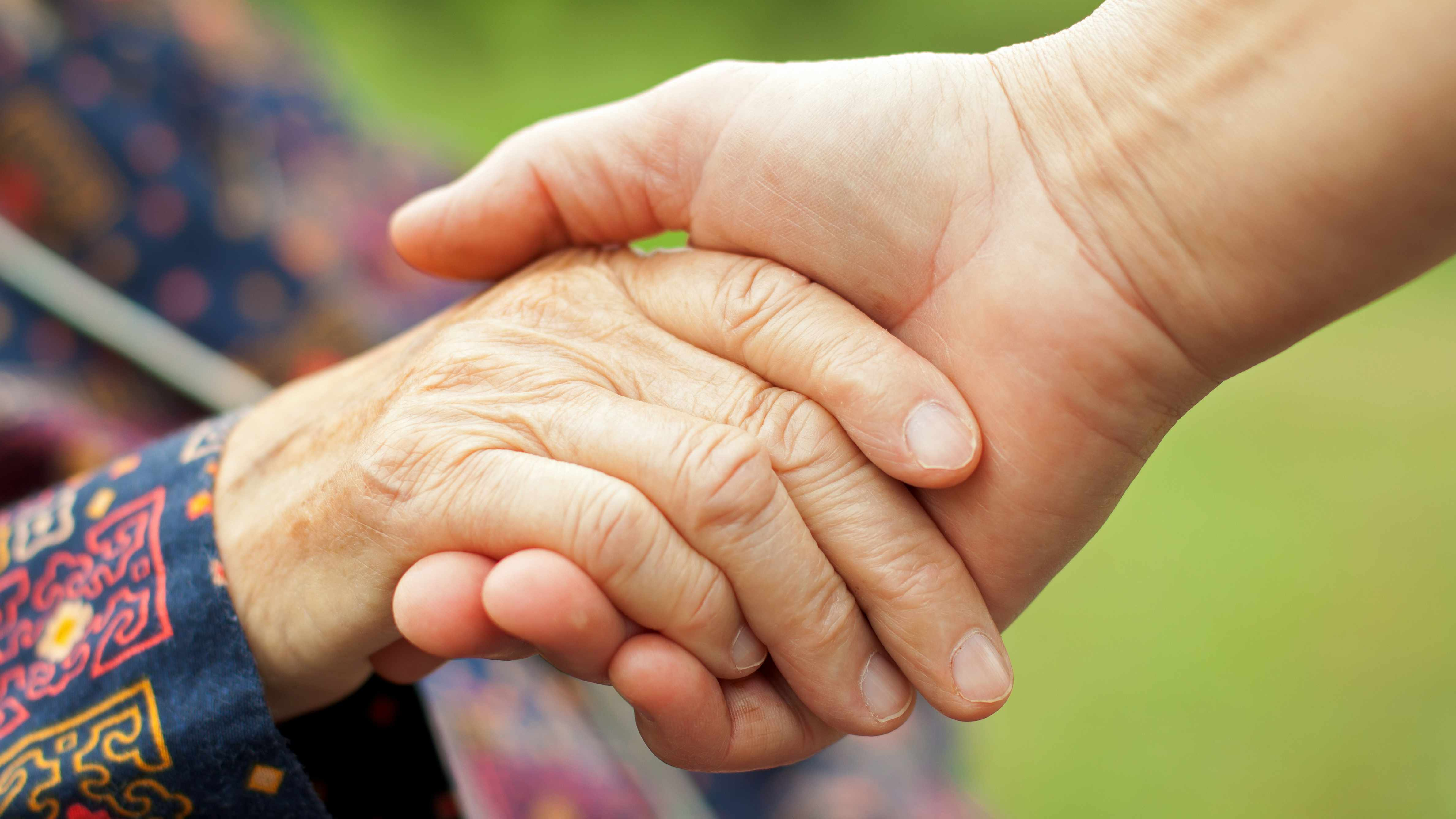 a caregiver holding the hand of an elderly person, senior citizen with arthritis, maybe Parkinson's disease