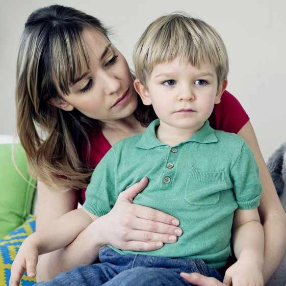 a little boy sitting on a woman's lap and he looks worried, sad about stomach ache