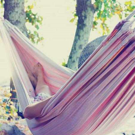 a person sleeping or napping in a hammock tied between the trees