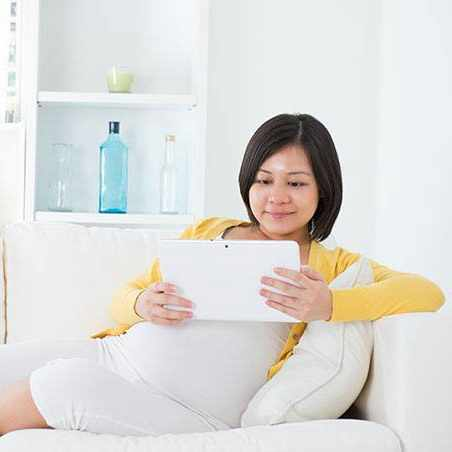 a pregnant woman sitting on a couch reading a book