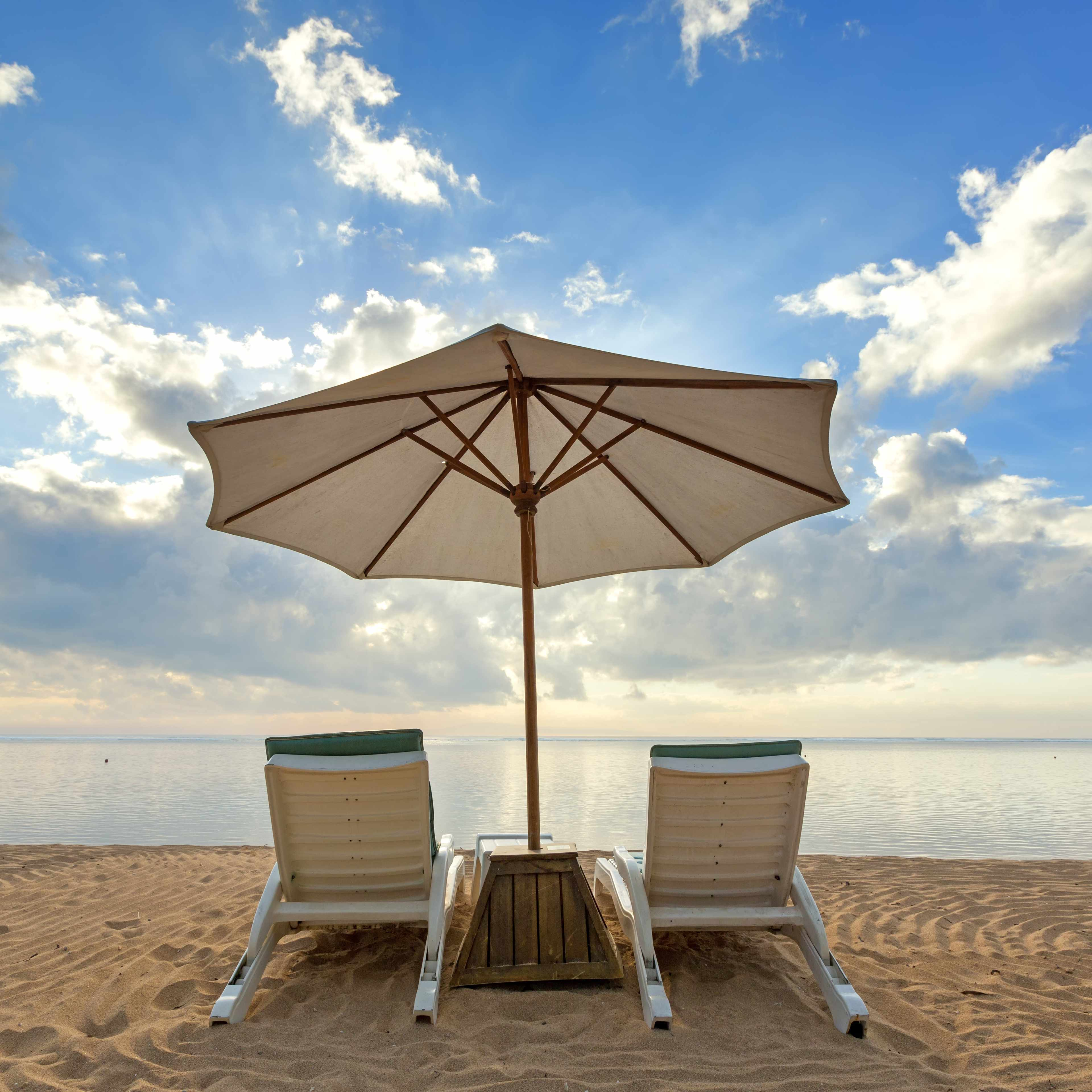 a sandy beach with two deck chairs and a large umbrella