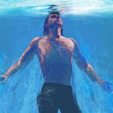 a young man under water swimming to the surface