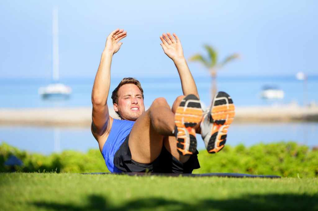 a man doing sit-ups exercising a workout outdoors