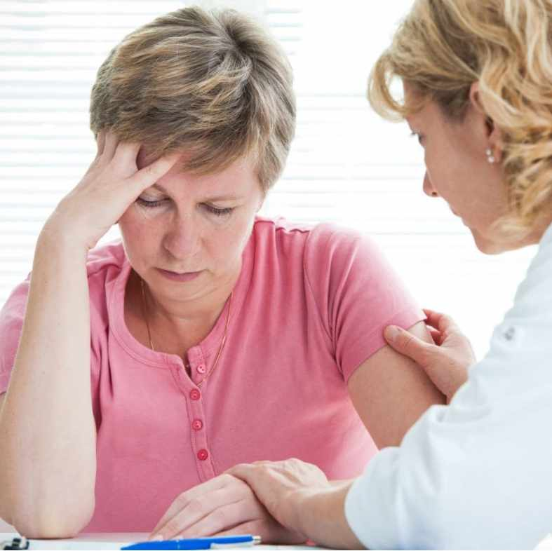 physician discussing diagnosis with female patient