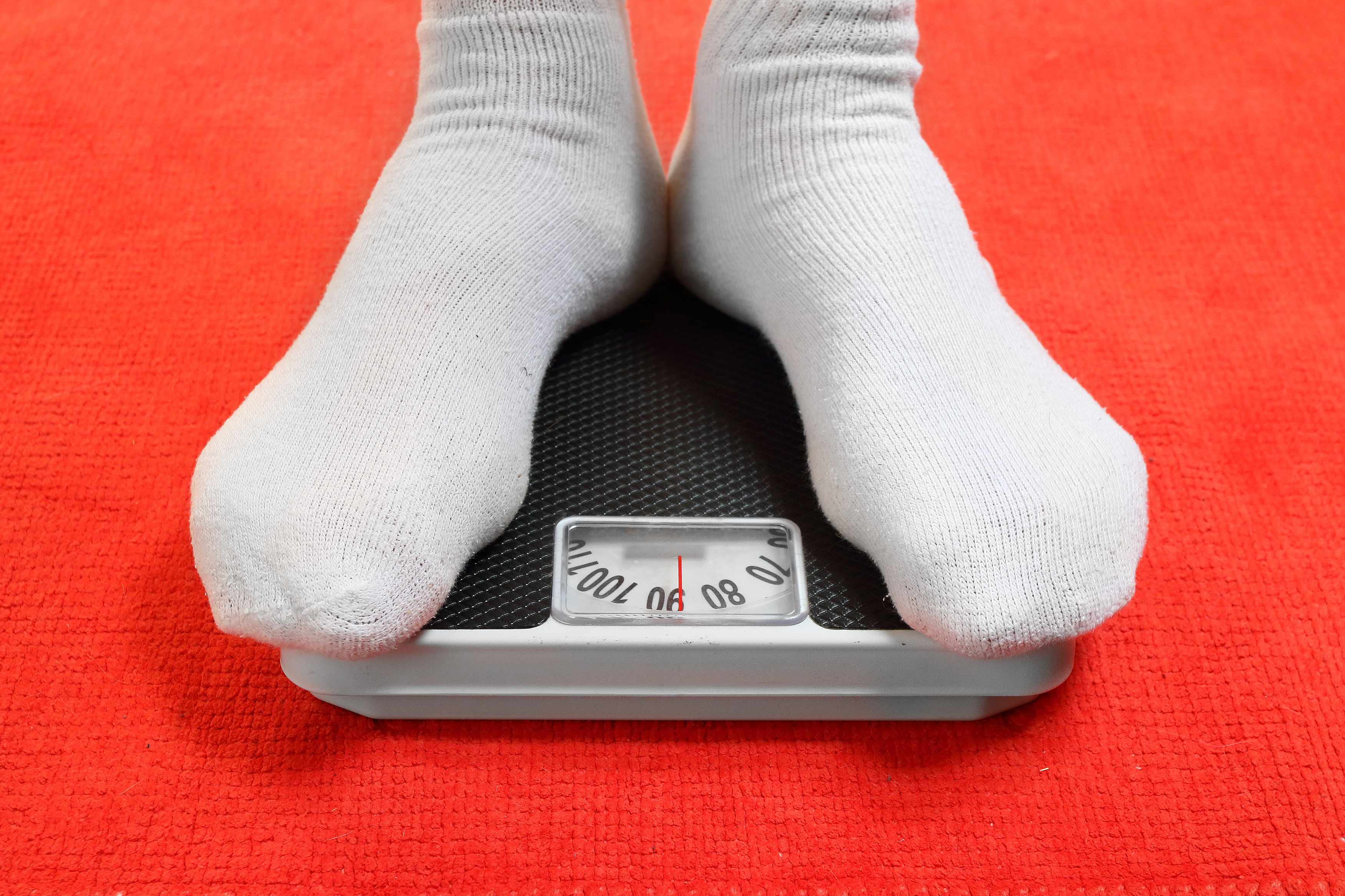 a young person in white socks checking weight on a scale
