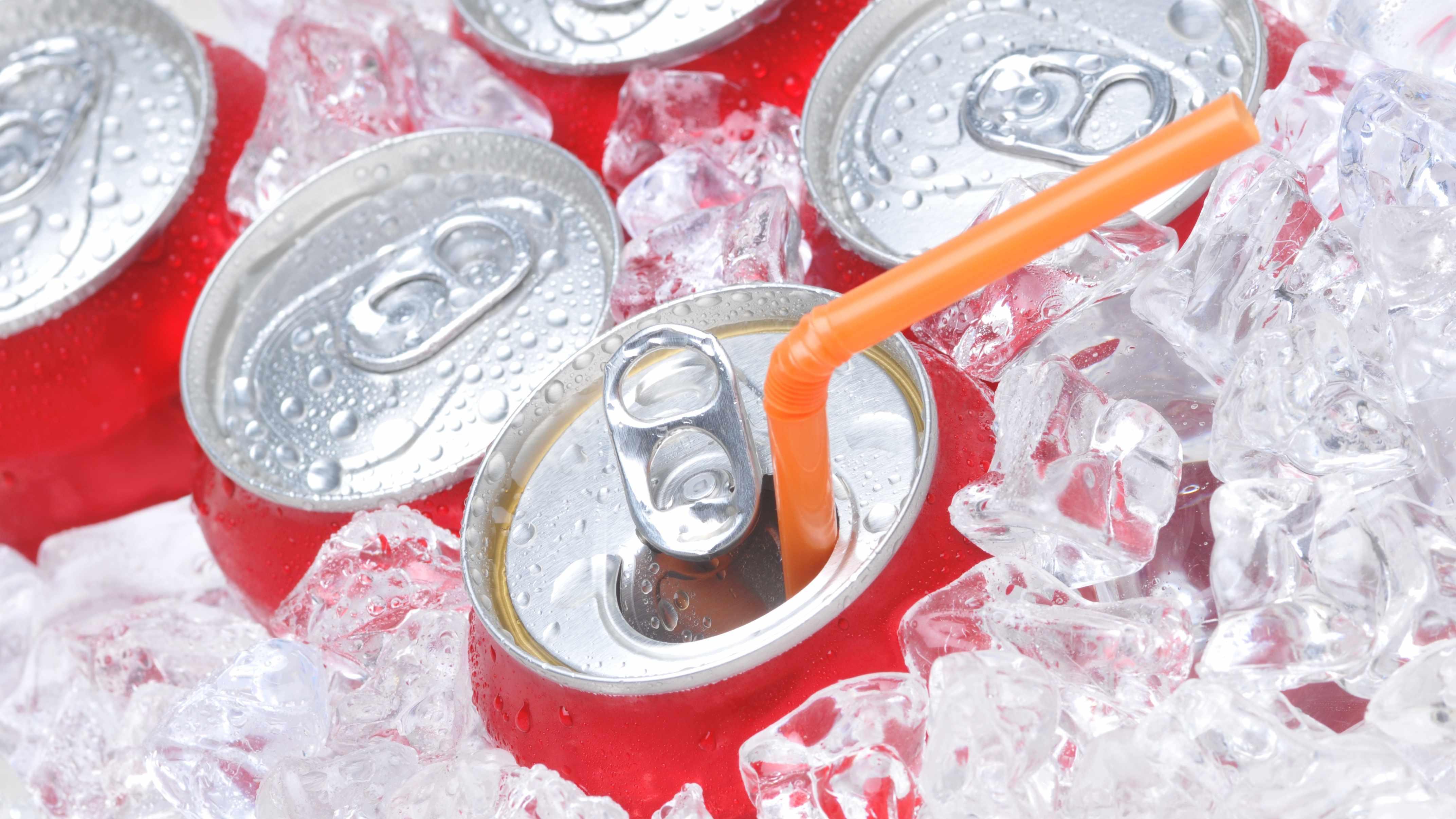 las tapas de varias latas de gaseosa aparecen sumergidas en hielo y una de ellas está abierta y tiene una pajita color naranja