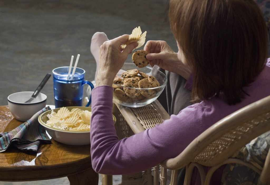 a woman seated, eating junk food, binge eating