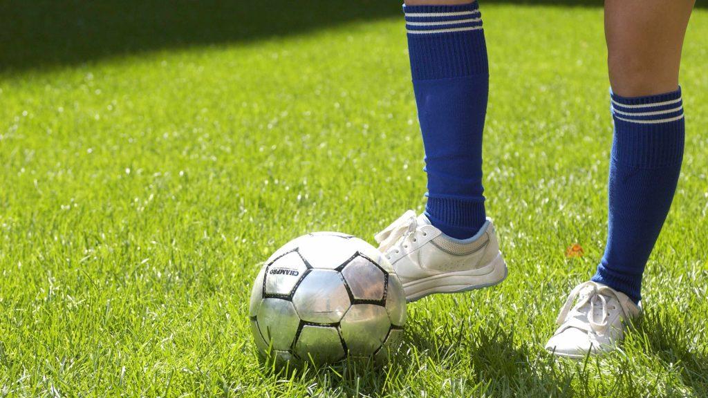Pie y pierna junto al balón de fútbol; pie pateando pelota de futbol