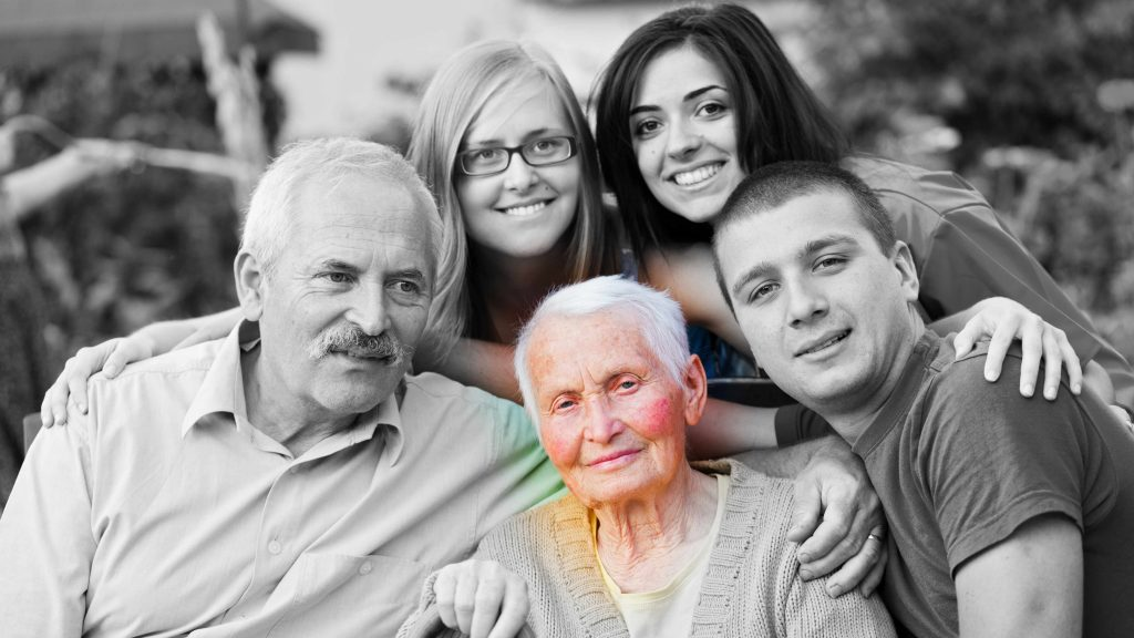 Foto familiar en blanco y negro donde, en color, aparece una anciana con aspecto triste y debilitado por alguna afección o por la enfermedad de Alzheimer