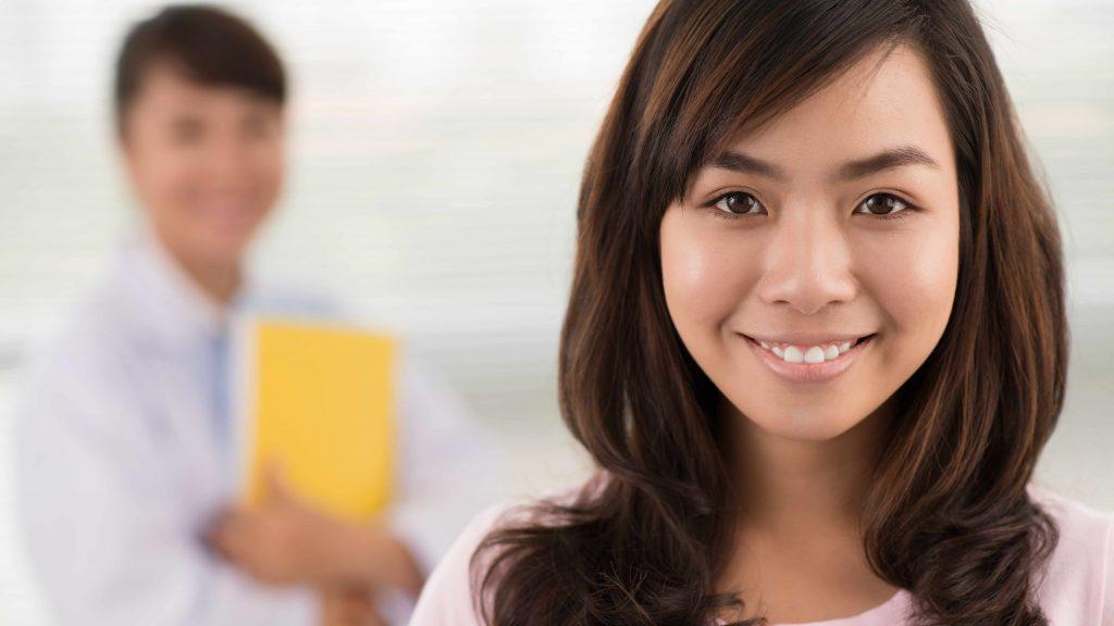Acercamiento de una mujer joven y sonriente, con una médica en el trasfondo