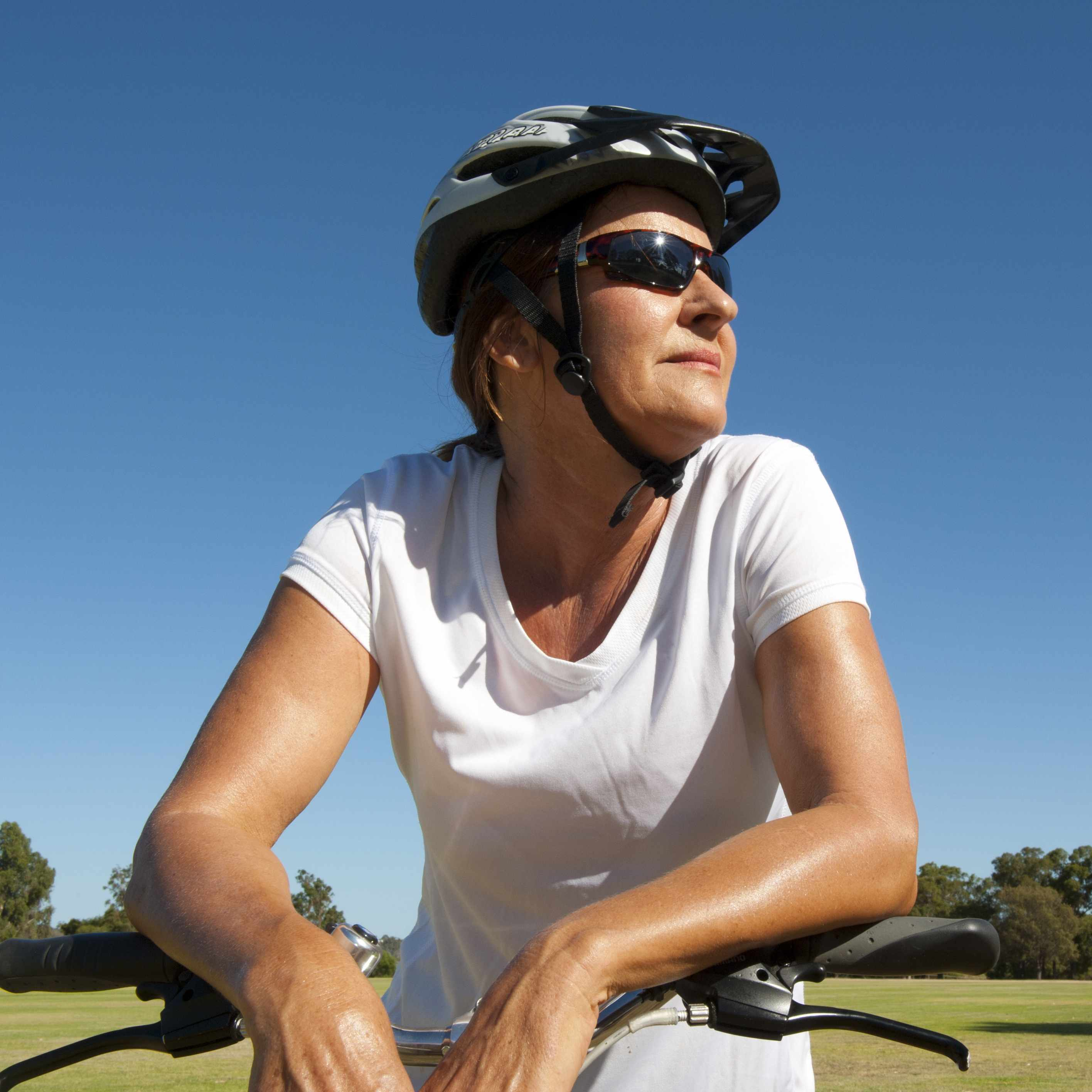 a woman outdoors on a sunny day, with a bike, wearing a helmet and sunglasses, sweating