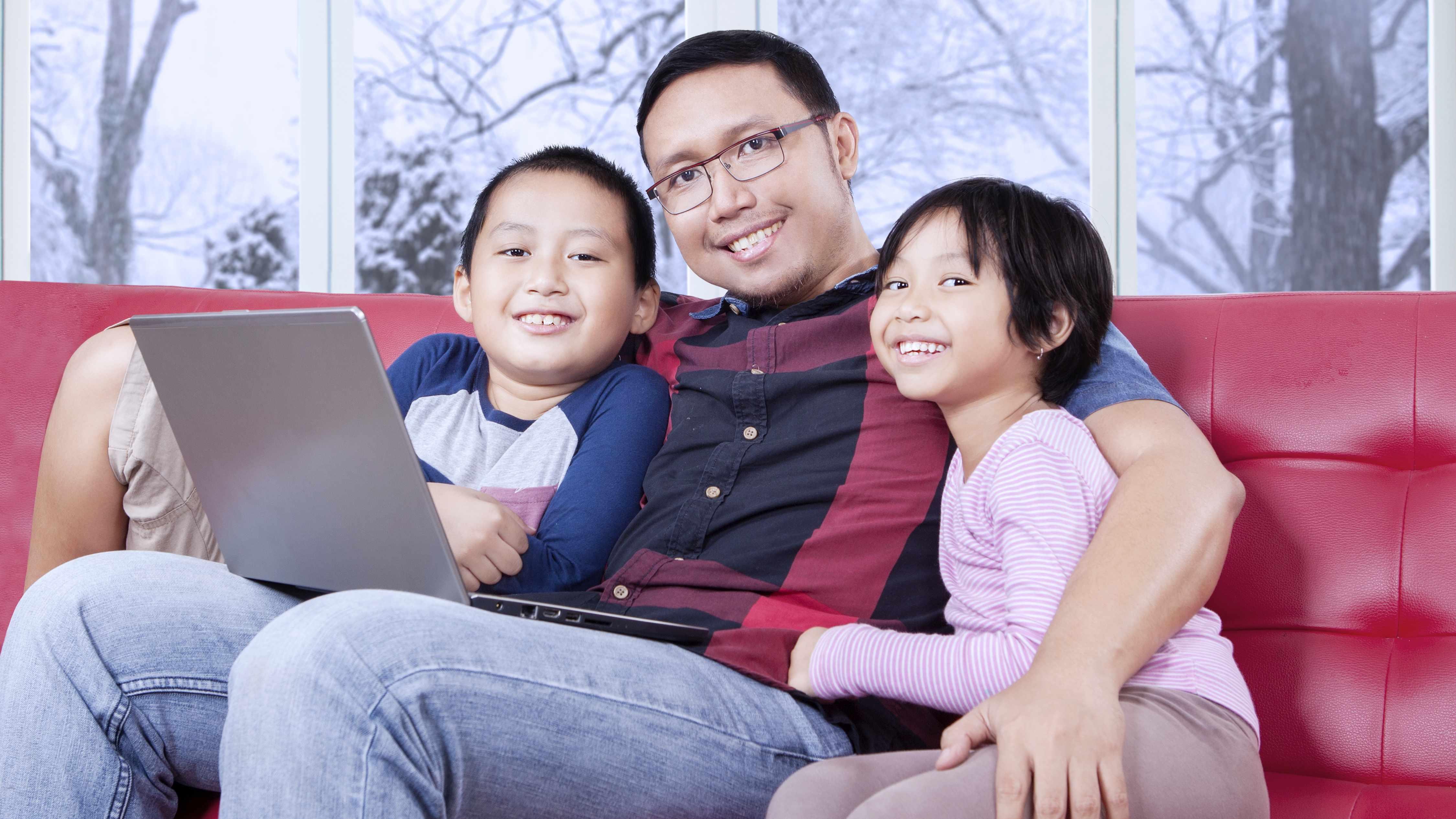 Un joven padre sentado en un sofá con sus hijos pequeños y una computadora portátil sobre las piernas sonríe y luce relajado