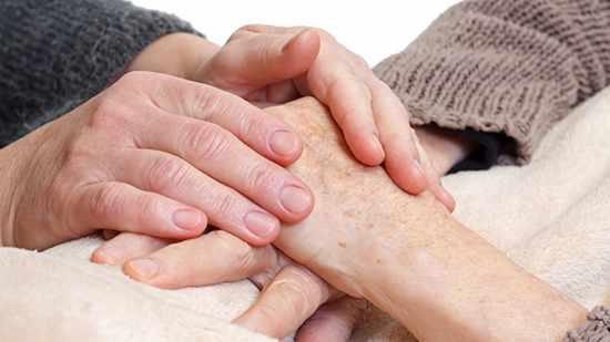 Un cuidador sostiene las manos de un paciente anciano