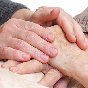 caregiver holding elderly patient's hands