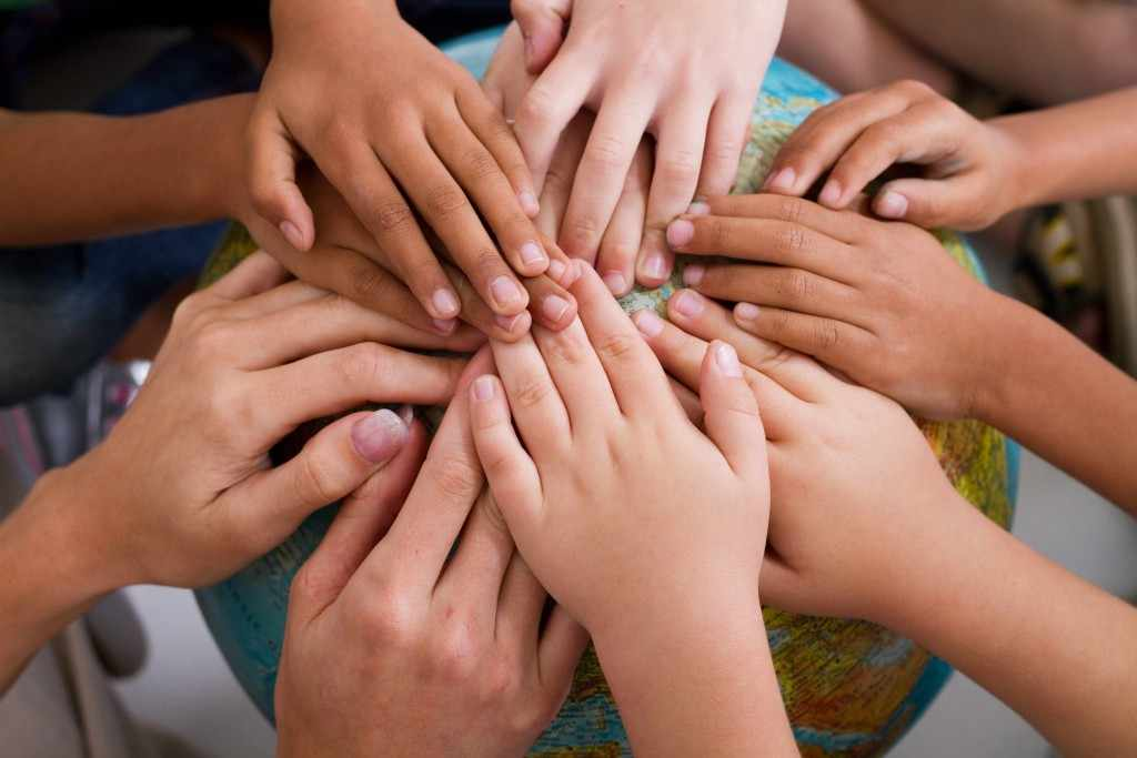 children's hands touching a globe representing world peace, friendships