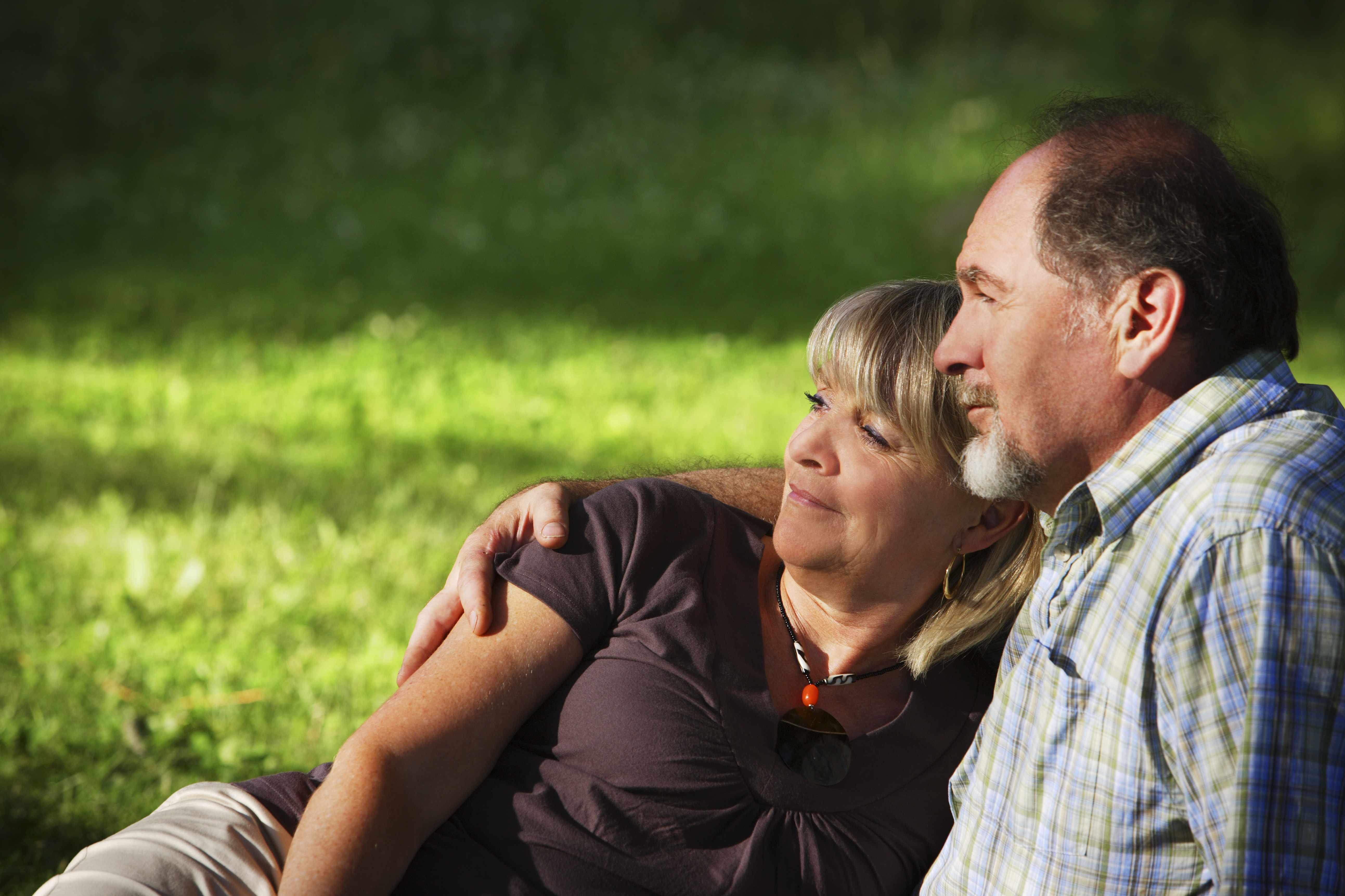 a middle-aged man and woman in each other's arms sitting outdoors in a park