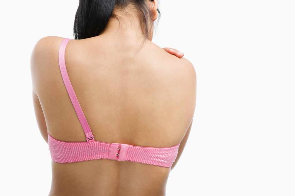 back of a woman in pink bra with one strap removed representing mastectomy