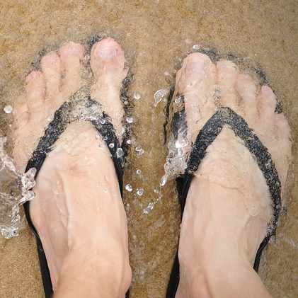 two people at the beach with flip flop sandals on their feet standing in sand with water covering their feet